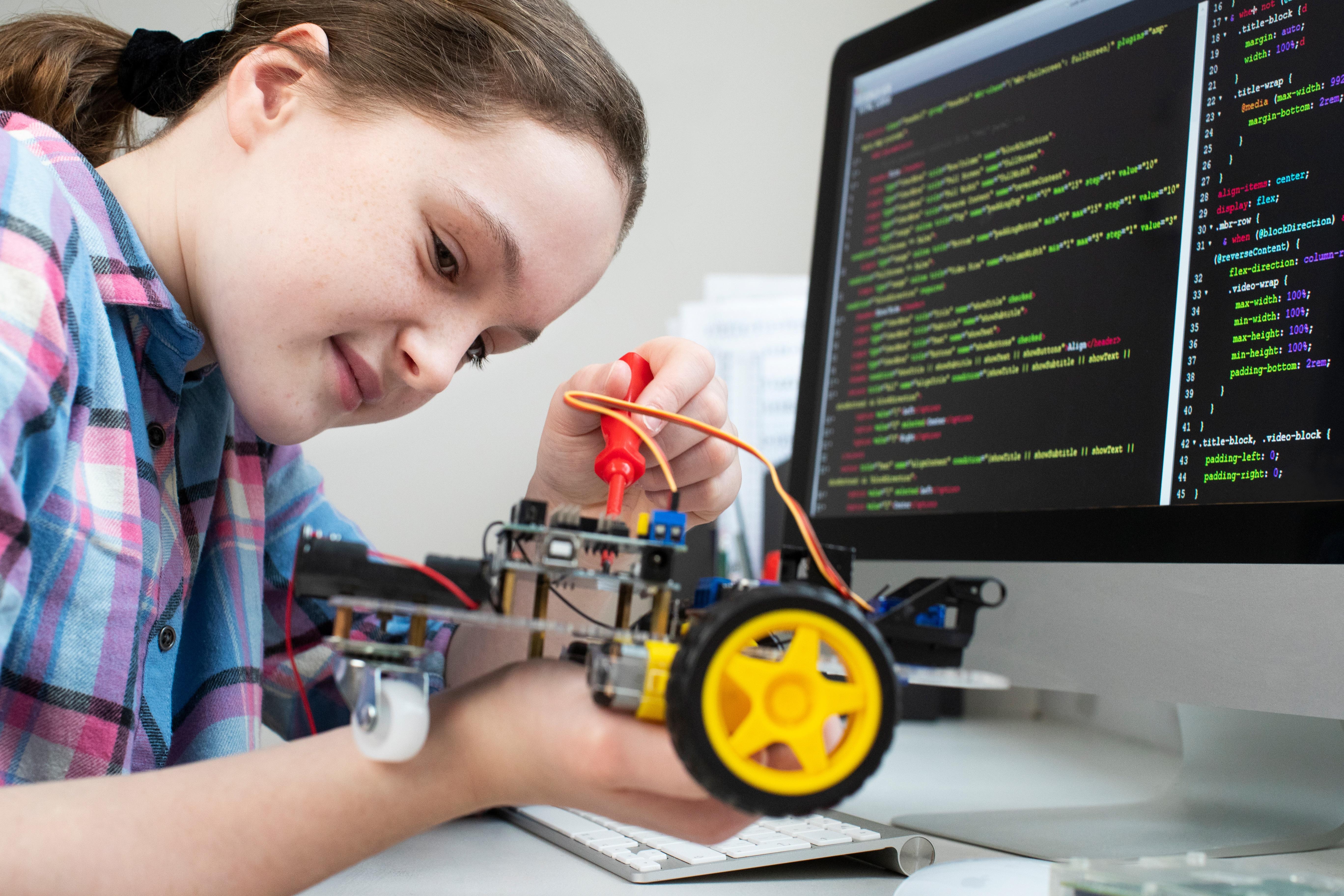Female Pupil Building Robotic Car In Science Lesson coding