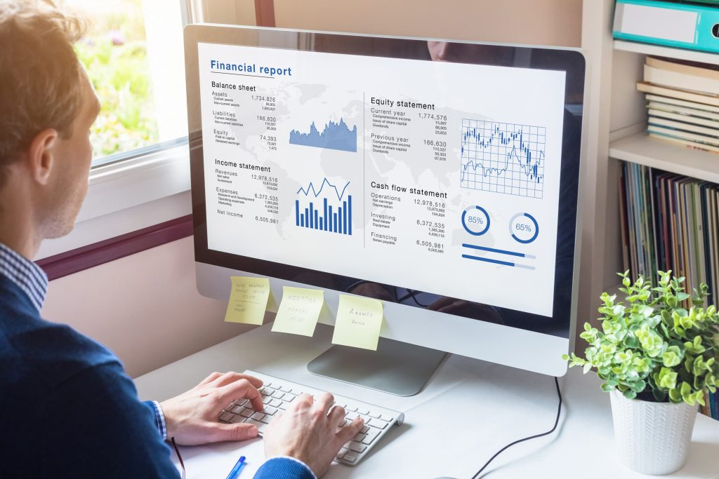 Businessman working on Financial Report of corporate operations on computer screen with Balance Sheet, Income Statement, and key performance indicators on custom software