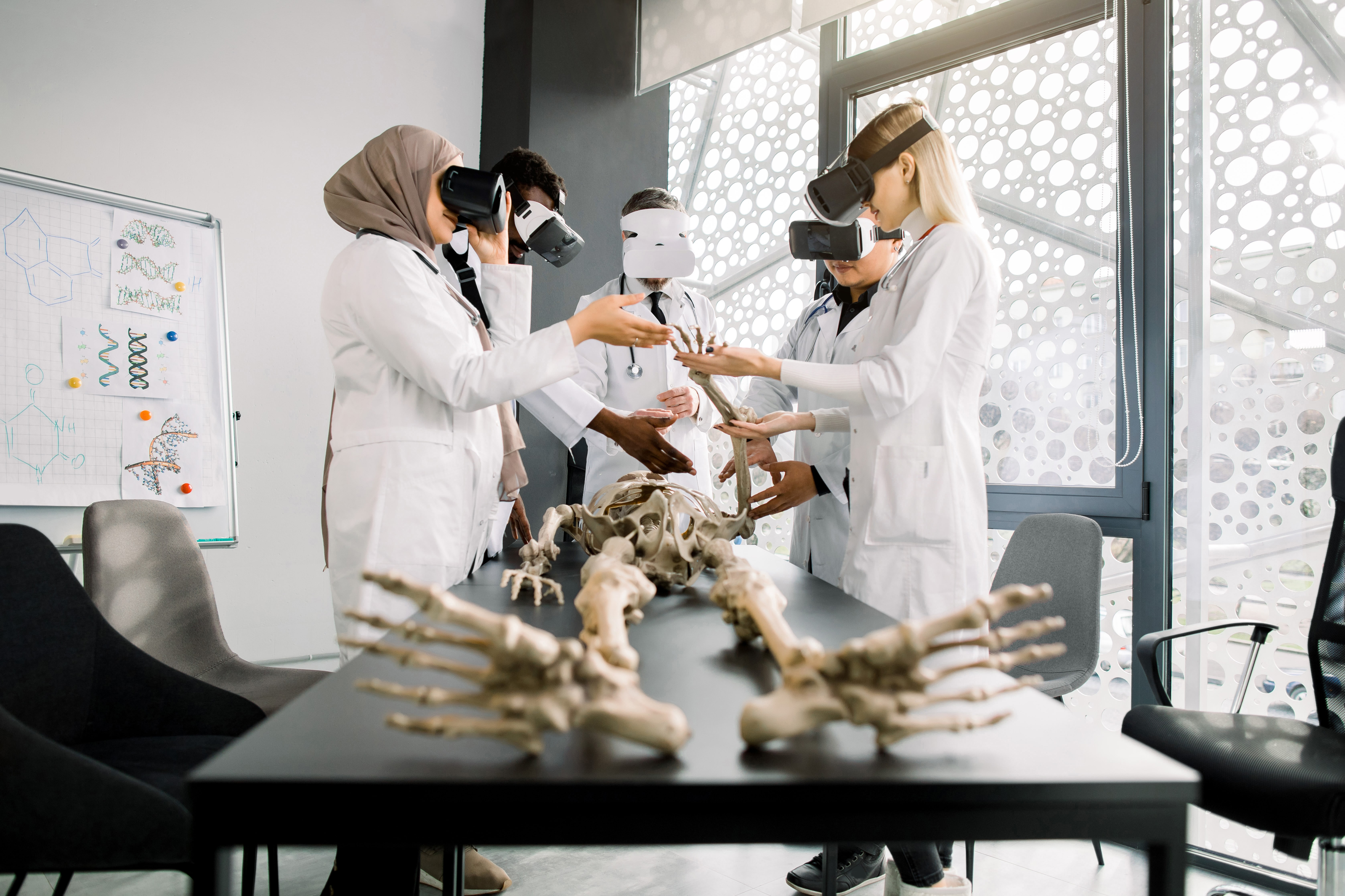 Male professor teacher using Virtual Reality Glasses to teach skeleton anatomy for multiethnic students in class. Education, VR, Tutoring, New Technologies and Teaching Methods concept, virtual reality for training