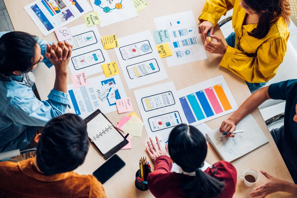 top view asian ux developer and ui designer brainstorming about mobile app interface wireframe design on table with customer brief and color code at modern office.Creative digital development agency, app development, custom software