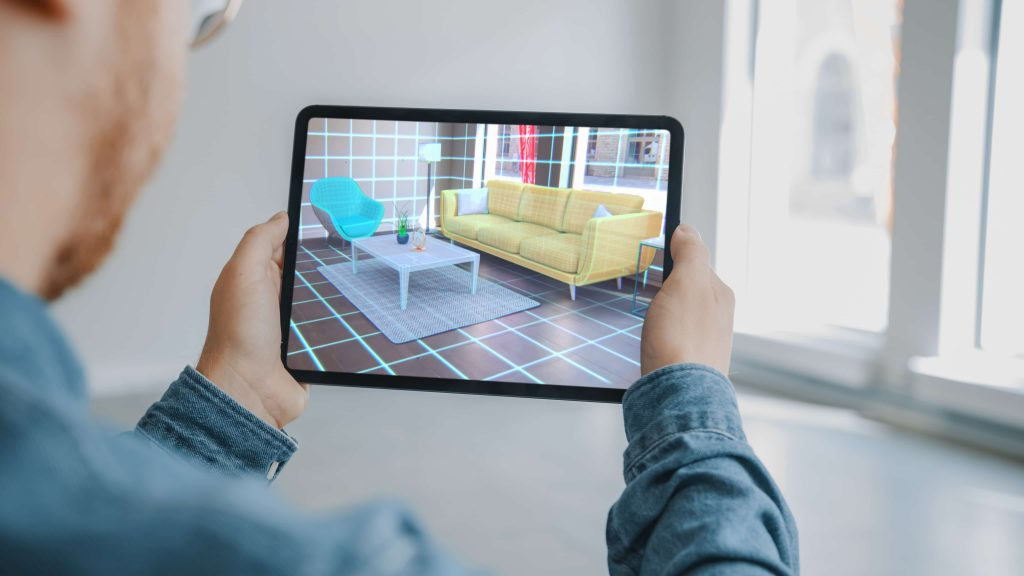 Decorating Apartment: Man Holding Digital Tablet with AR Interior Design Software Chooses 3D Furniture for Home. Man is Choosing Sofa, Table for Living Room. Over Shoulder Screen Shot with 3D Render with augmented reality mobile app